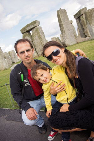 Happy family of three, mom, dad and little toddler boy, posing for the camera at Stonehenge on a cloudy summer day