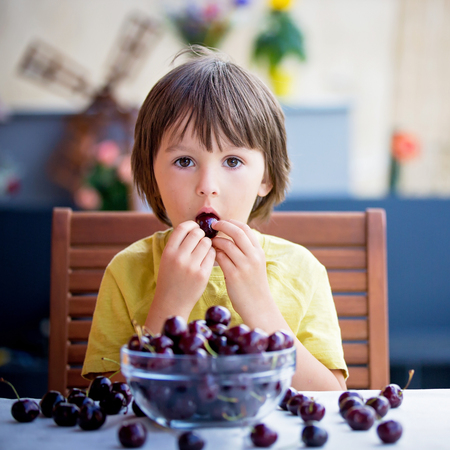 Cute little boy, eating sweet cherry outdoors, sitting on table