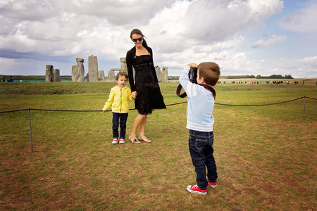 Young child, boy, taking pic of his mom and brother with digital camera at Stonehenge, family happiness concept Stock Photo