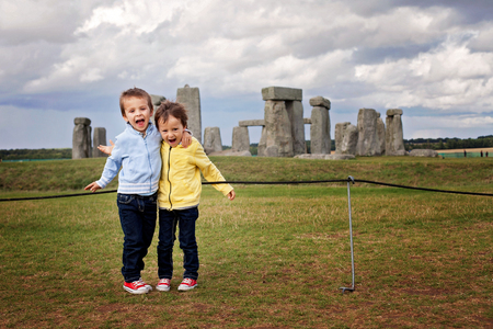 Two children, boy brothers, posing for the camera in front of Stonehenge in England, happily smiling, laughing and hugging Stock Photo