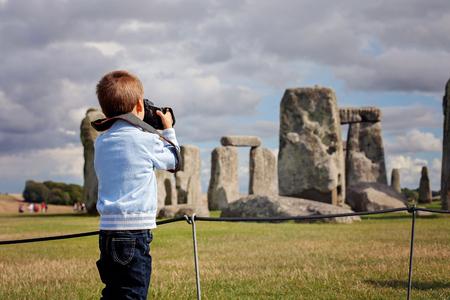 어린 아이, 소년, 흐린 날에 스톤 헨지에서 디지털 카메라로 사진을 찍고