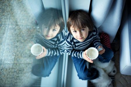 Adorable little preschool child, boy, drinking milk, sitting on window shield, reflecting on the window
