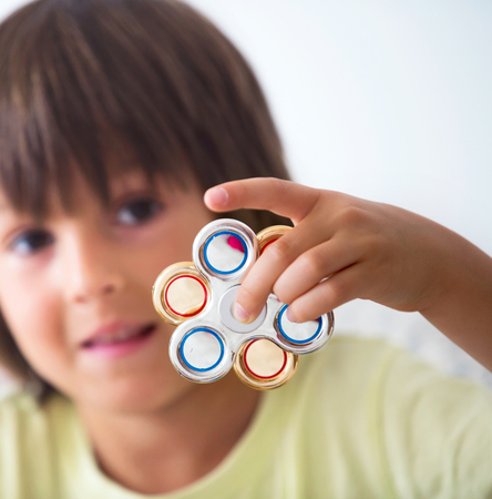 Jonge jongens spelen met fidget spinner stress verlichting speelgoed thuis