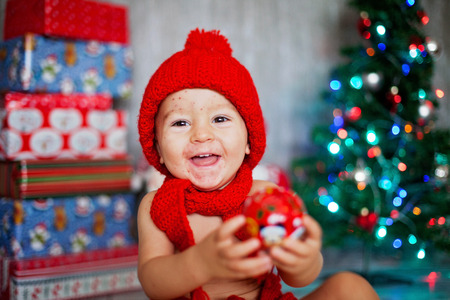 Sweet toddler boy with chickenpox, varicella zoster virus, with christmas hat on xmas, playing with toys Stock Photo