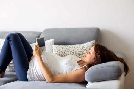 Young pregnant woman, lying down on couch in living room, reading on tablet
