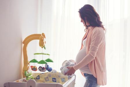 젊은 임신 매력적인 여자, 그녀의 신생아, 아름 다운 백 라이트에 대 한 준비 아기 침대