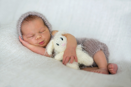 Newborn baby boy, sleeping peacefully wrapped in knitted wrap