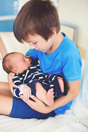 Cute boy, brother, meeting for the first time his new baby brother at hospital, day after delivery Stock Photo