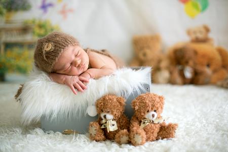 Il neonato sveglio dorme con i giocattoli, orsacchiotti intorno a lui