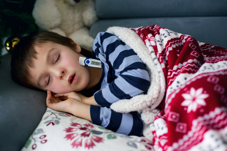 couch: Sick little child, boy, with high fever sleeping on the couch at home, lots of medicine on the table Stock Photo
