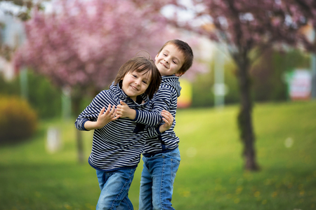 Two children, brothers, fighting in a park, springtime Banco de Imagens