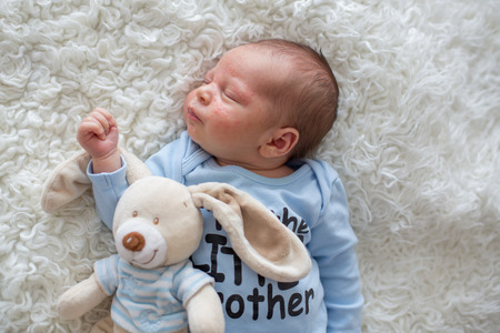 Little newborn baby sleeping with toy, baby with scin rash, child dermatitis symptom problem rash, newborn suffering atopic symptom on skin. concept child health