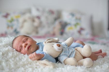 Kleine pasgeboren baby slapen met speelgoed, baby met huiduitslag, kinderdermatitis symptoom probleemuitslag, pasgeboren lijdend atopisch symptoom op de huid. Concept kind gezondheid