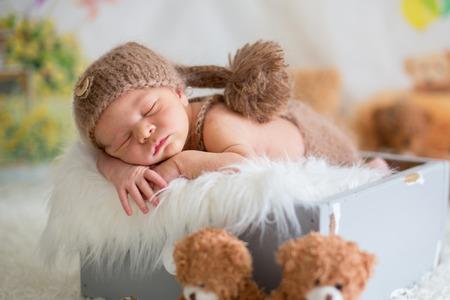 Cute newborn baby sleeps with a toys, teddy bears around him