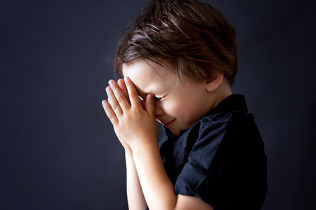 Little boy praying, child praying, isolated black background Stock fotó