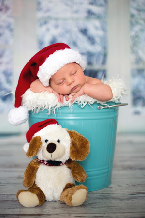 Portrait of a newborn baby boy,l wearing christmas hat, sleeping in a blue bucket, toys, christmas decoration and lantern around him, by the window, snow outside. Banco de Imagens - 85539032