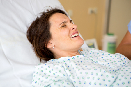Pregnant woman in delivery room, having contractions