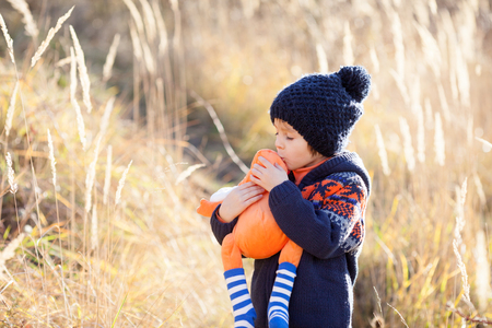 Cute little caucasian child, boy, holding fluffy toy, hugging it, in the park, on sunny winter day