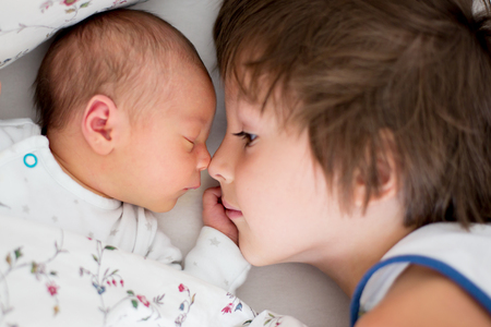 Beautiful boy, hugging with tenderness and care his newborn baby brother at home. Family love happiness concept Stock Photo