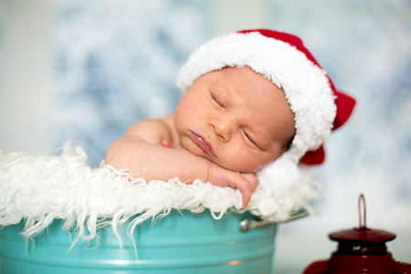 Portrait of a newborn baby boy,l wearing christmas hat, sleeping in a blue bucket, toys, christmas decoration and lantern around him, by the window, snow outside. Banco de Imagens