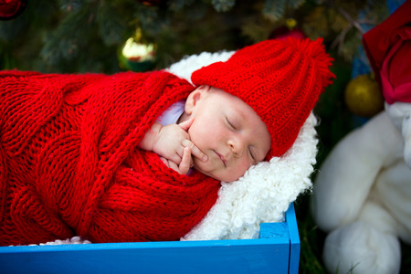 Portrait of newborn baby in Santa clothes lying under Christmas tree, outdoors