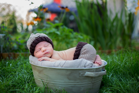 Little sweet newborn baby boy, sleeping in crate with knitted pants and hat in garden, outdoors in the park