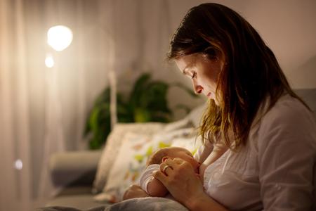 Jonge mooie moeder, die haar pasgeboren babyjongen de borst geven bij nacht, schemerig licht. Mam, borstvoeding zuigeling