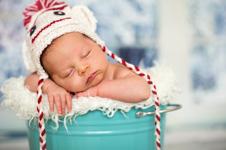 portrait of a newborn baby boyl wearing christmas hat sleeping in a blue