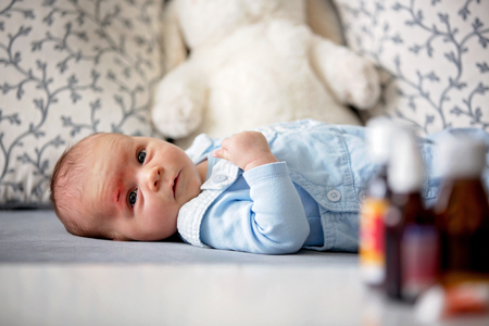 Little newborn baby with little wound on his forehead, scratch Stock Photo