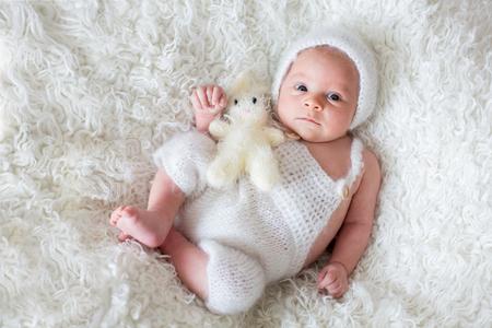 Beautiful newborn baby boy, looking curiously at camera, smiling