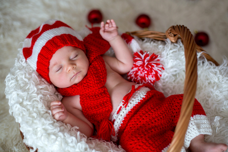 Little sleeping newborn baby boy, wearing Santa hat and pants, holding toy Stock Photo