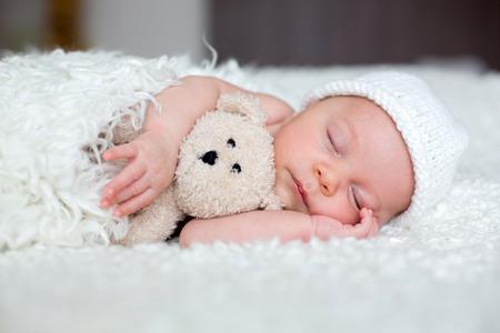 Beautiful newborn baby boy, sleeping with little toy Banco de Imagens