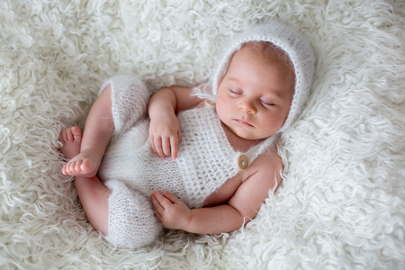 Beautiful newborn baby boy, sleeping with little toy Imagens
