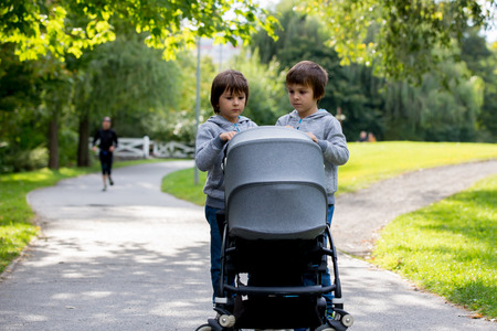 Two children, boys, pushing stroller with little baby in the park
