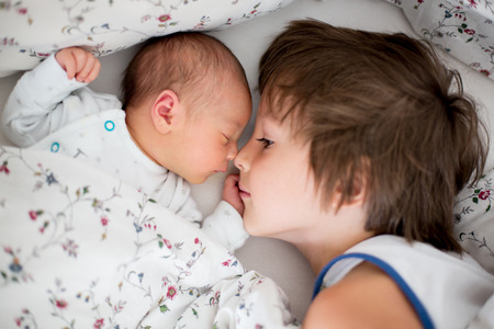 Beautiful boy, hugging with tenderness and care his newborn baby brother at home. Family love happiness concept Imagens
