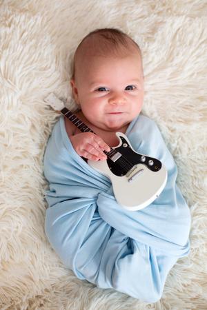 신생아 아기, 파란색 스카프에 싸여, 작은 기타를 들고 웃 고