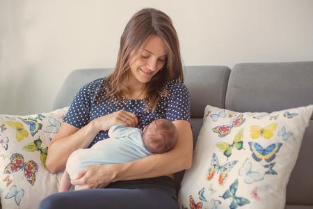 jeune mère allaitant son bébé nouveau-né à la maison