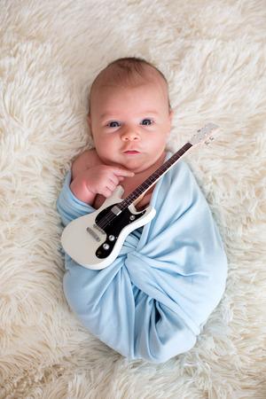 신생아 아기, 파란색 스카프에 싸여, 작은 기타를 들고 웃 고 스톡 콘텐츠 - 86946643