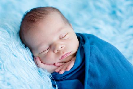 Cute baby boy, peacefully sleeping wrapped in blue wrap on a blue fur Standard-Bild