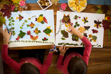 Sweet children, boys, applying leaves using glue while doing arts and crafts in school, autumn time