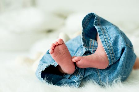 작은 아기 소년 발, 아기는 오후에 침대에 누워 자연 채광