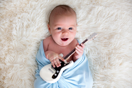 Newborn baby boy, wrapped in blue scarf, holding a little guitar and smiling Stock fotó