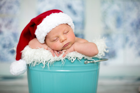 Portrait of a newborn baby boy,l wearing christmas hat, sleeping in a blue bucket, toys, christmas decoration and lantern around him, by the window, snow outside. Banco de Imagens - 86897398