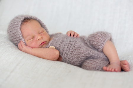 Newborn baby boy, sleeping peacefully wrapped in knitted wrap Stock Photo - 86946652