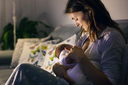 젊은 아름 다운 어머니, 밤, 흐린 빛 그녀의 신생아 아기를 모유 수 유. 모유 수유중인 엄마 스톡 콘텐츠