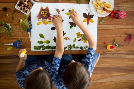 甘い子供たち、男の子、学校で芸術や工芸品をしながら、接着剤を使用して葉を適用し、秋の時間