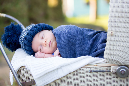 Little newborn baby boy, sleeping in old retro stroller in forest, autumn time, wrapped in scarf and knitted hat. Posed baby in retro pram, infant sleeping in vintage stroller in the woods