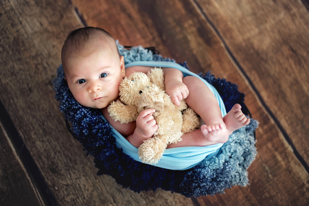 Little newborn baby boy, looking curiously at camera, posed picture