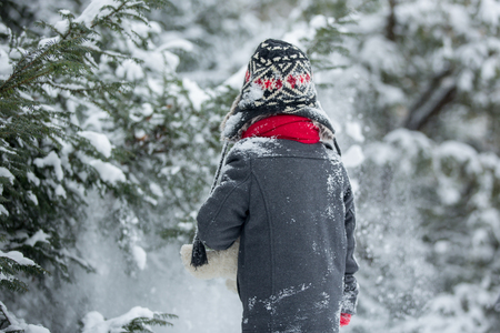 Sad lost child, boy in a forest with teddy bear, wintertime in the snow Stock Photo