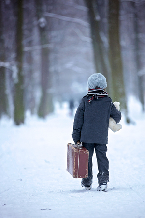Sad child, boy, walking in a forest with old suitcase and teddy bear, wintertime in the snow 免版税图像